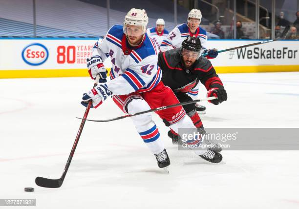 Brendan Smith of the New York Rangers plays the puck against Vincent Trocheck of the Carolina Hurricanes during the second period in Game One of the...