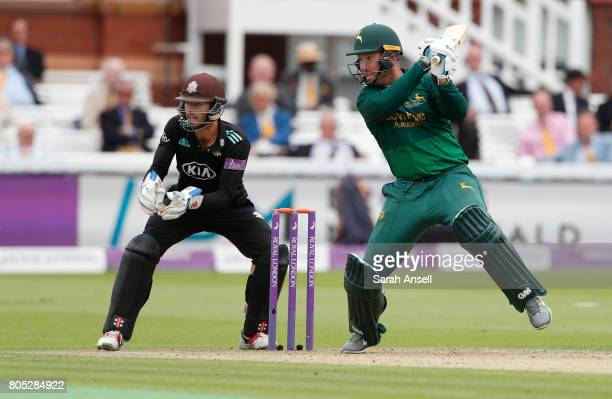 Brendan Taylor of Nottinghamshire hits out as Surrey wicket keeper Ben Foakes looks on during the match between Nottinghamshire and Surrey at Lord's...