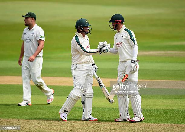 Brendan Taylor of Nottinghamshire is congratulated by Alex Hales on reaching his half century during the LV County Championship match between...