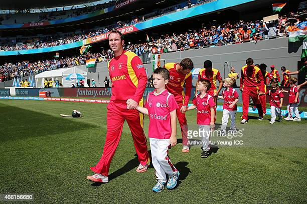 Brendan Taylor of Zimbabwe leads his team on to the field during the 2015 ICC Cricket World Cup match between India and Zimbabwe at Eden Park on...