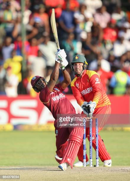 Brendan Taylor of Zimbabwe looks on as Rovman Powell of The West Indies scores runs during The Cricket World Cup Qualifier between The West Indies...