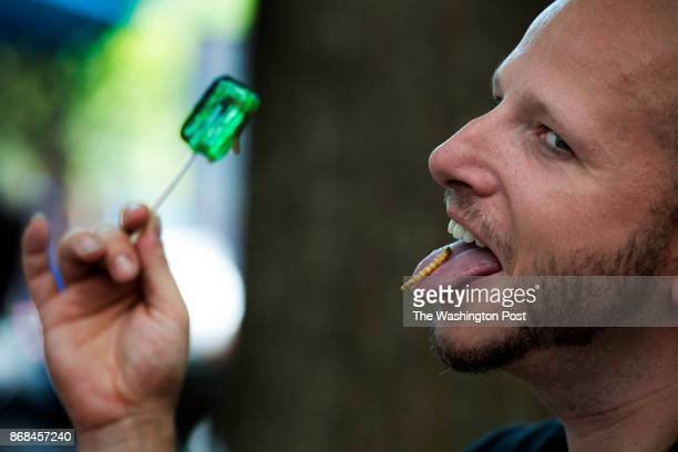 Brendan 'Twig' Sheppard poses while eating a roasted mealworm at a charity event at Occidental Grill in Washington DC on June 4 2014 It's all part of...