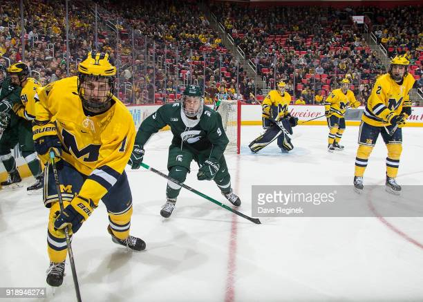Brendan Warren of the Michigan Wolverines skates after a loose puck in front of Mitchell Lewandowski of the Michigan State Spartans during the Duel...