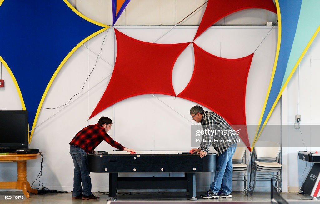 Brendan Young plays air hockey with David Conrad of PLS Services/Strive at Strive in South Portland Wednesday, February 14, 2018.