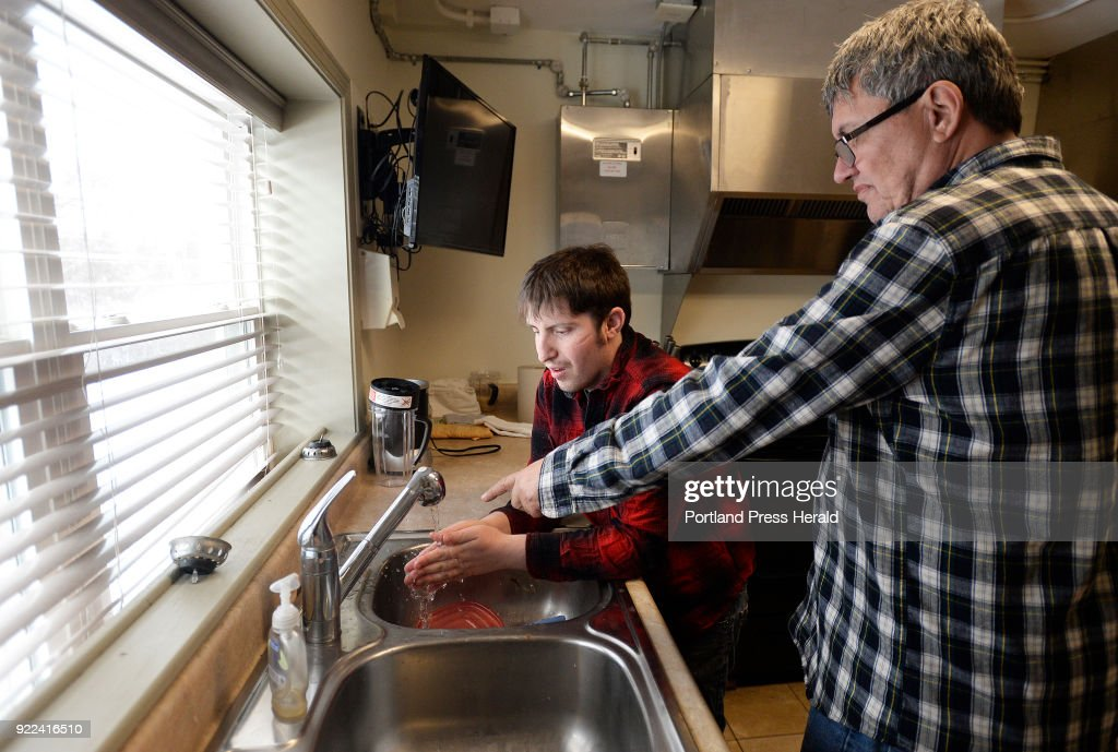 Brendan Young, who has intellectual disabilities, washes his hands during cooking group at STRIVE in South Portland as David Conrad of PLS Services/Strive gives him some assistance Wednesday, February 14, 2018.