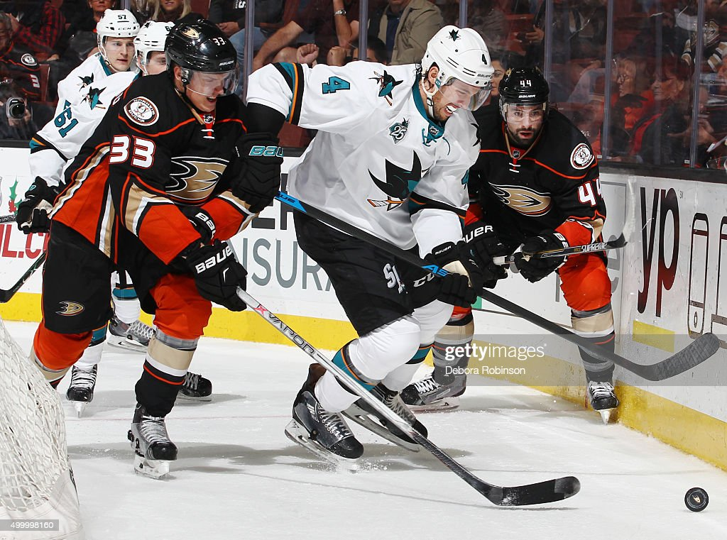 Brenden Dillon #4 of the San Jose Sharks battles for the puck against Jakob Silfverberg #33 and Nate Thompson #44 of the Anaheim Ducks on December 4, 2015 at Honda Center in Anaheim, California.