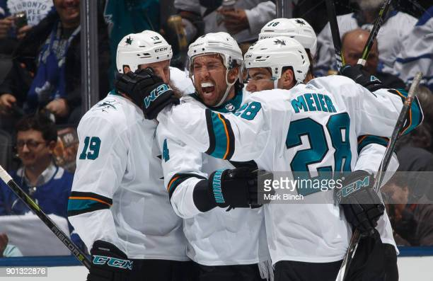 Brenden Dillon of the San Jose Sharks celebrates his goal against the Toronto Maple Leafs with teammates Joe Thornton and Timo Meier during the first...