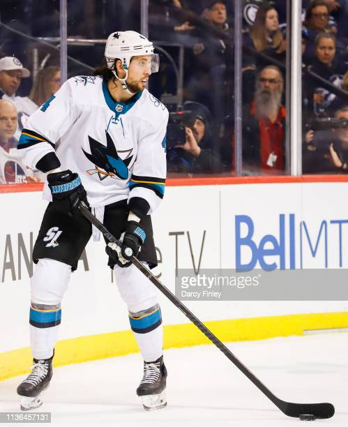 Brenden Dillon of the San Jose Sharks plays the puck along the boards during second period action against the Winnipeg Jets at the Bell MTS Place on...