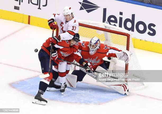 Brenden Dillon of the Washington Capitals and Andrei Svechnikov of the Carolina Hurricanes collide in front of Vitek Vanecek of the Capitals in the...