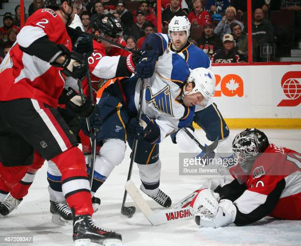 Brenden Morrow of the St Louis Blues gets hit in front of Robin Lehner of the Ottawa Senators during the first period at the Canadian Tire Centre on...