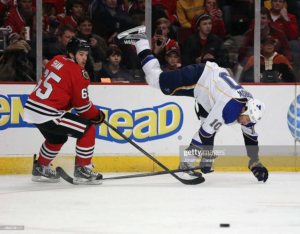 Brenden Morrow #10 of the St. Louis Blues tries to keep his balance after colliding with Andrew Shaw #65 of the Chicago Blackhawks at the United Center on March 19, 2014 in Chicago, Illinois.