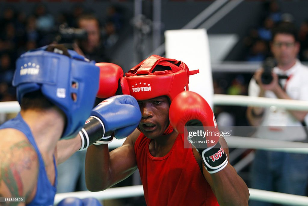 Brendo Coelho of Braazil (red) fights with Edwin Bennet of Ecuador (blue) during the Men's 64kg Boxing Finals as part of the I ODESUR South American Youth Games at Coliseo Miguel Grau on September 25, 2013 in Lima, Peru.