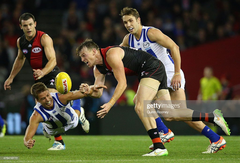 Brendon Goddard of the Bombers handballs whilst being tackled by Andrew Swallow of the Kangaroos during the round seven AFL match between the Essendon Bombers and the North Melbourne Kangaroos at Etihad Stadium on May 15, 2015 in Melbourne, Australia.