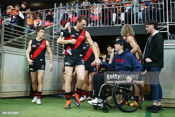 Brendon Goddard of the Bombers walks out onto the ground with Will Murray before the the round 11 AFL match between the Greater Western Sydney Giants...