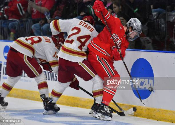 Brendon Kearney of the Ohio State Buckeyes battles for the puck against Colin Staub and Ryan Barrow of the Denver Pioneers during an NCAA Division I...