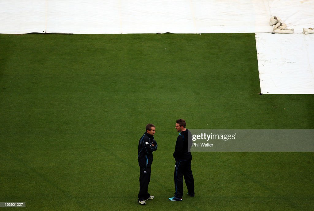 Brendon McCullum of New Zealand (R) and coach Mike Hesson (L) survey the conditions as rain delays the start of play on day five of the second test match between New Zealand and England at the Basin Reserve on March 18, 2013 in Wellington, New Zealand.