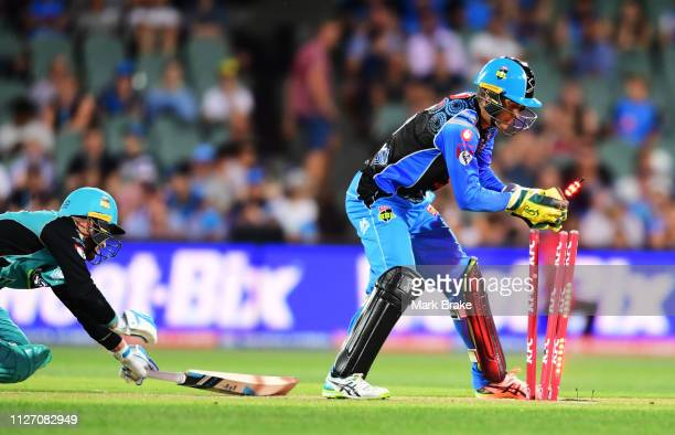 Brendon McCullum of the Heat makes it to his crease as Alex Carey of the Adelaide Strikers takes off the bails during the Big Bash League match...