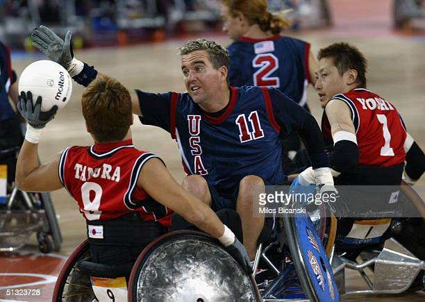 Brenet Popen of USA battles Tamura Manabu of Japan during the Wheelchair Rugby mach between USA and Japan at the Athens 2004 Paralympic Games on...