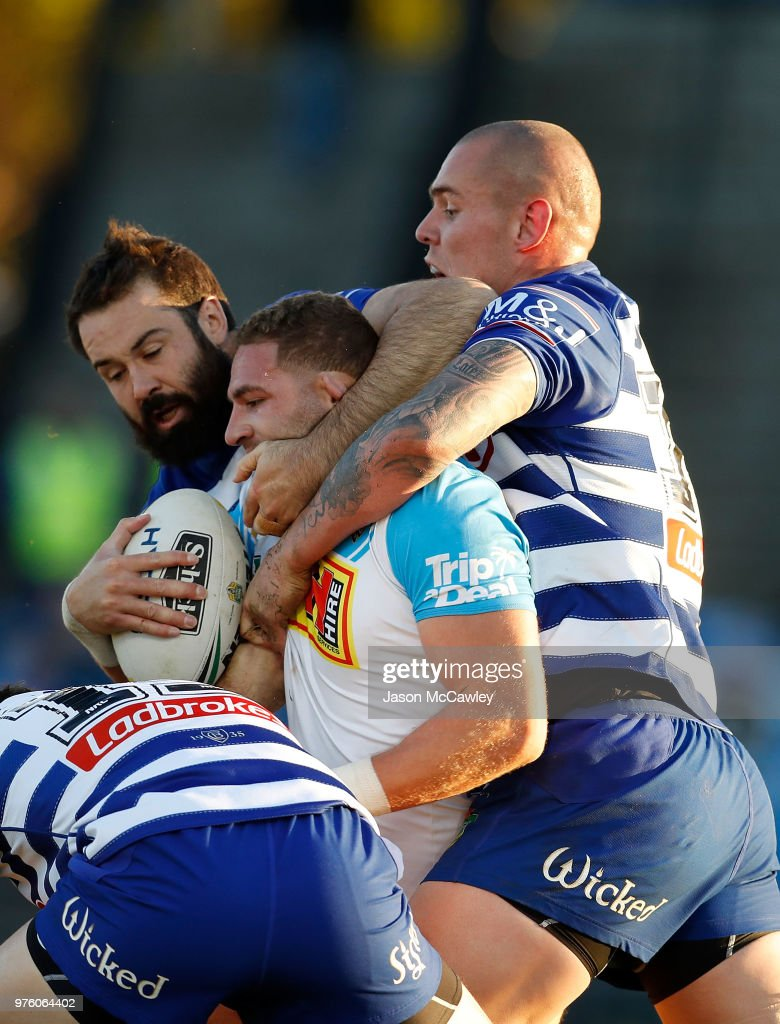 Brenko Lee of the Titans is tackled Aaron Woods and David Klemmer of the Bulldogs during the round 15 NRL match between the Canterbury Bulldogs and the Gold Coast Titans at Belmore Sports Ground on June 16, 2018 in Sydney, Australia.