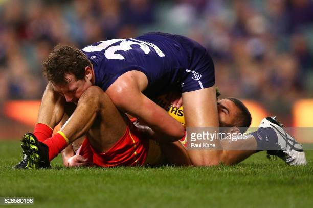 Brennan Cox of the Dockers tackles Adam Saad of the Suns during the round 20 AFL match between the Fremantle Dockers and the Gold Coast Suns at...