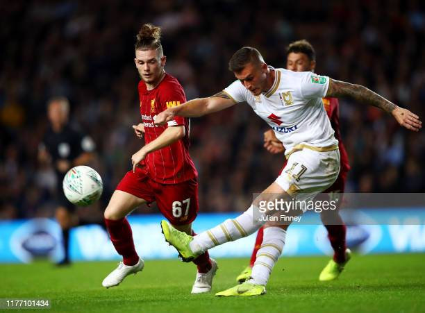 Brennan Dickenson of MK Dons shoots as Harvey Elliott of Liverpool looks on during the Carabao Cup Third Round match between Milton Keynes Dons and...