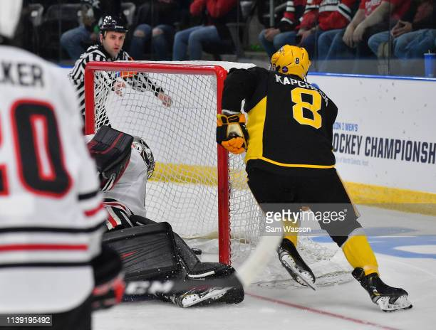 Brennan Kapcheck of the American International Yellow Jackets scores against David Hrenak of the St Cloud State Huskies during an NCAA Division I...