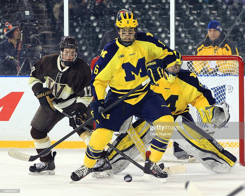 Brennan Serville #6 of the University of Michigan Wolverines goes after a loose puck in front Justin Kovacs #17 of the Westen Michigan Broncos during game two of the Hockeytown Winter Festival Great Lakes Invitational - Day 1 played outdoors at Comerica Park on December 27, 2013 in Detroit, Michigan. The Broncos won 3-2 in O.T.