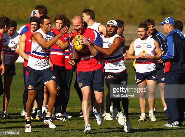 Brennan Stack and Nathan Djerrkura of the Bulldogs try to strip the ball from Barry Hall during a Western Bulldogs AFL training session at Whitten...