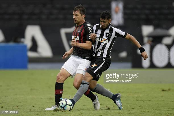 Brenner of Botafogo struggles for the ball with Paulo Andre of Atletico PR during the match between Botafogo and Atletico PR as part of Brasileirao...