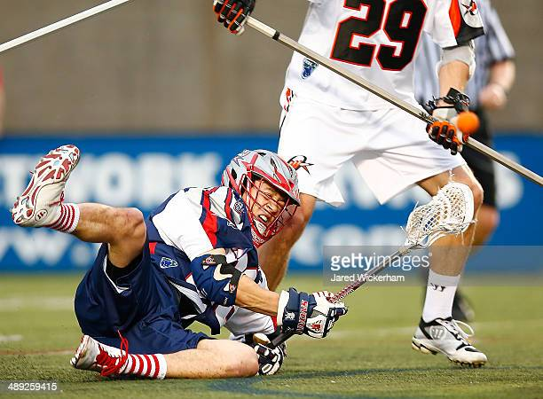 Brent Adams of the Boston Cannons falls while taking a shot in the first half against the Denver Outlaws at Harvard Stadium on May 10, 2014 in...