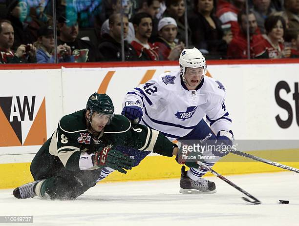Brent Burns of the Minnesota Wild and Tyler Bozak of the Toronto Maple Leafs battle for the puck at the Xcel Energy Center on March 22 2011 in St...