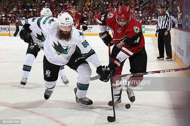 Brent Burns of the San Jose Sharks and Anthony Duclair of the Arizona Coyotes battle for a loose puck during the first period of the NHL game at Gila...
