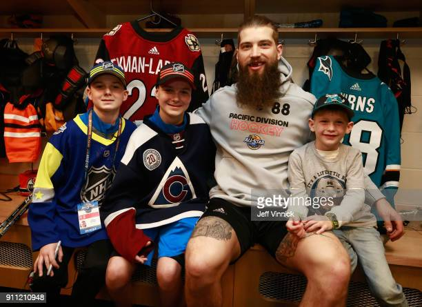 Brent Burns of the San Jose Sharks and his son pose with MakeAWish kid Felix Powers and his brother in the locker room before 2018 GEICO NHL AllStar...