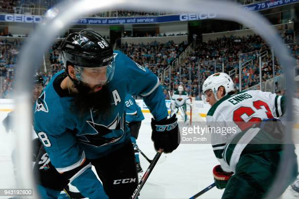 Brent Burns of the San Jose Sharks and Tyler Ennis of the Minnesota Wild battle in the corner at SAP Center on April 7 2018 in San Jose California