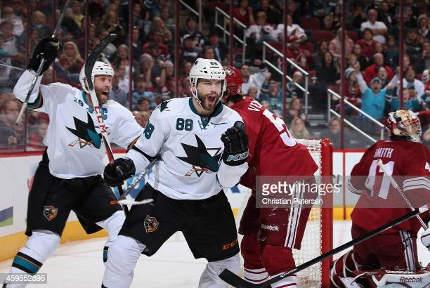 Brent Burns of the San Jose Sharks celebrates alongside Joe Thornton after Burns scored a third period goal past goaltender Mike Smith of the Phoenix...