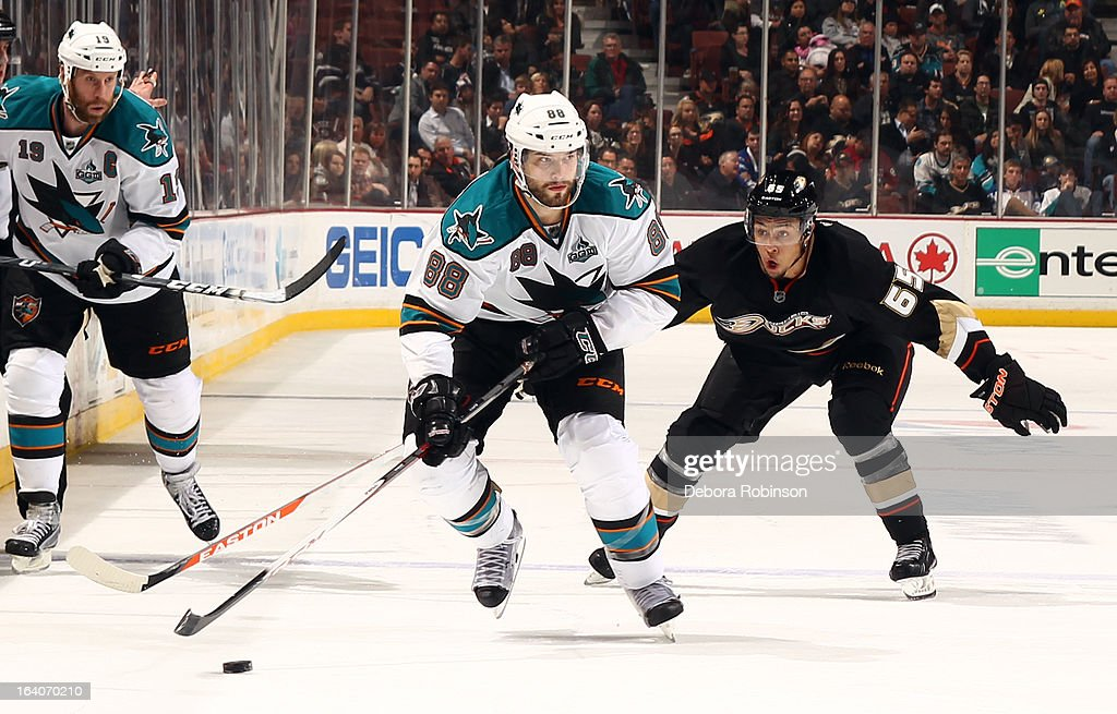 Brent Burns #88 of the San Jose Sharks handles the puck against Emerson Etem #65 of the Anaheim Ducks on March 18, 2013 at Honda Center in Anaheim, California.