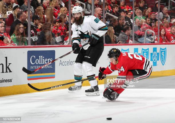 Brent Burns of the San Jose Sharks hits the puck past Dominik Kahun of the Chicago Blackhawks in the second period at the United Center on December...
