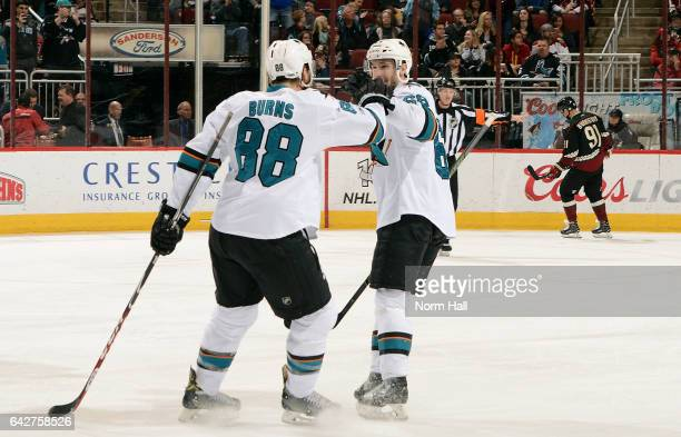 Brent Burns of the San Jose Sharks is congratulated by teammate Melker Karlsson after scoring a first period goal against the Arizona Coyotes at Gila...