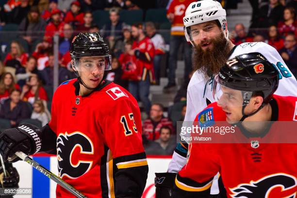 Brent Burns of the San Jose Sharks jokes with Johnny Gaudreau and Garnet Hathaway of the Calgary Flames in a game against the San Jose Sharks at the...