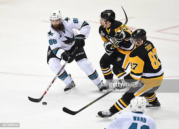 Brent Burns of the San Jose Sharks oves the puck in front of Conor Sheary and Sidney Crosby of the Pittsburgh Penguins during Game One of the 2016...