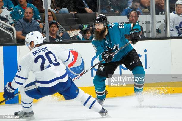 Brent Burns of the San Jose Sharks passes the puck in front of Dominic Moore of the Toronto Maple Leafs at SAP Center on October 30 2017 in San Jose...