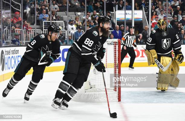 Brent Burns of the San Jose Sharks plays the puck around the net followed by teammate Joe Pavelski of the San Jose Sharks as goaltender MarcAndre...
