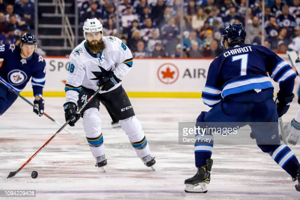 Brent Burns of the San Jose Sharks plays the puck down the ice as Ben Chiarot of the Winnipeg Jets defends during third period action at the Bell MTS...
