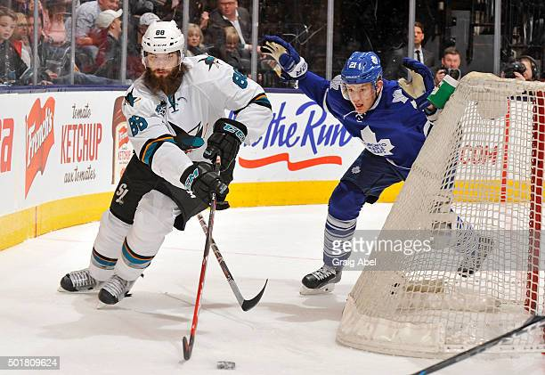 Brent Burns of the San Jose Sharks skates the puck away from James van Riemsdyk of the Toronto Maple Leafs during NHL game action December 17 2015 at...