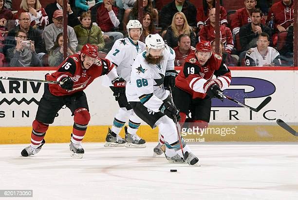 Brent Burns of the San Jose Sharks skates with the puck away from Brad Richardson and Shane Doan of the Arizona Coyotes during the first period at...