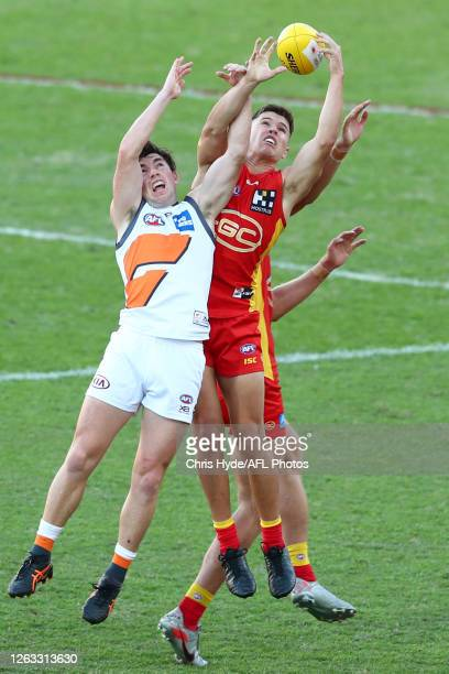 Brent Daniel and Connor Budarick of the Suns compete for the ball during the round nine AFL match between Gold Coast Suns and the Greater Western...