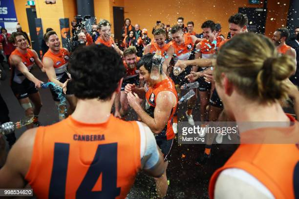 Brent Daniels of the Giants and team mates celebrate victory after the round 17 AFL match between the Greater Western Sydney Giants and the Richmond...