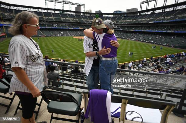 Brent Doeden aka 'Captain Earthman' gets a hug from Diana Barrett as he and his wife Becky Scharfenberg left arrive to Coors Field for the Colorado...