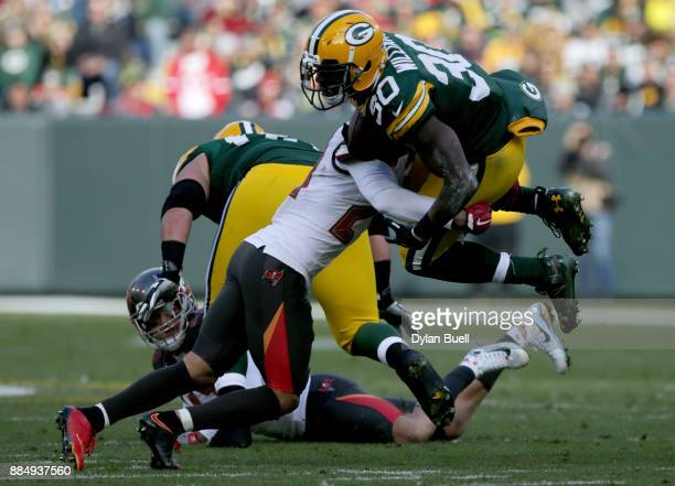 Brent Grimes of the Tampa Bay Buccaneers tackle Jamaal Williams of the Green Bay Packers in the first quarter at Lambeau Field on December 3 2017 in...