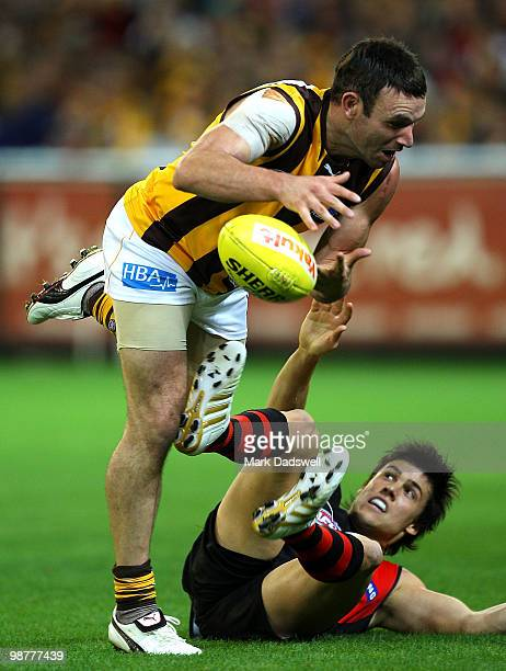 Brent Guerra of the Hawks gathers the ball over Angus Monfries of the Bombers during the 6 AFL match between the Essendon Bombers and the Hawthorn...